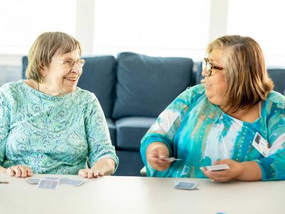 A resident and staff member playing cards
