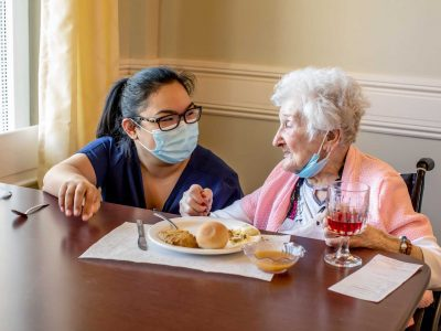 A staff member speaking with a resident during meal time.